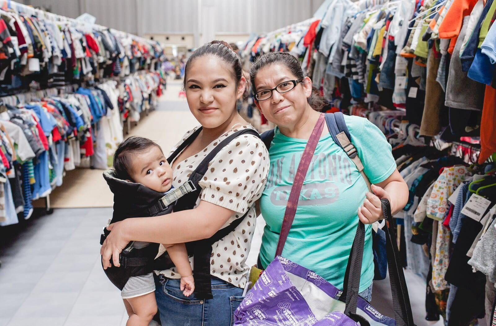 Grandmom, mom and baby in a carrier gather together and flash a smile as they shop for baby items.