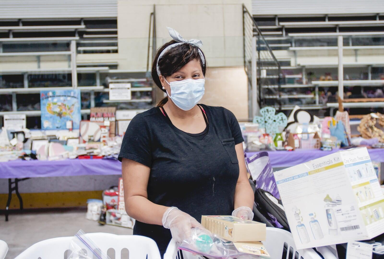 A masked Team Member with gloves helps out at a local JBF sale.